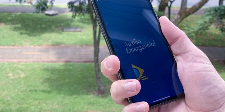 auxílio emergencial aprovado: a imagem mostra mão segurando celular aberto no app do auxílio emergencial