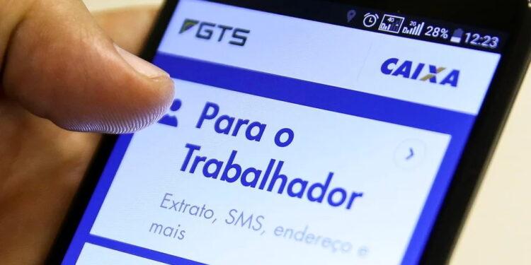 Saque do FGTS: enquadramento em mão mexendo em celular. Na tela, é possível ver a página do FGTS