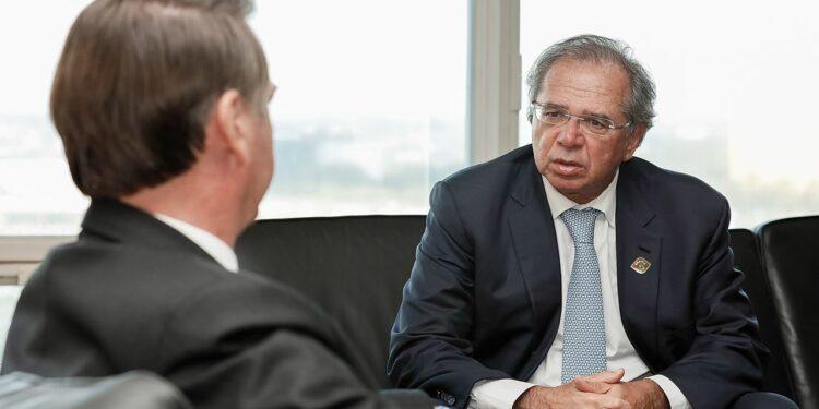 ampliação do bolsa família: a imagem mostra o presidente jair bolsonaro sentado em frente ao ministro Paulo Guedes