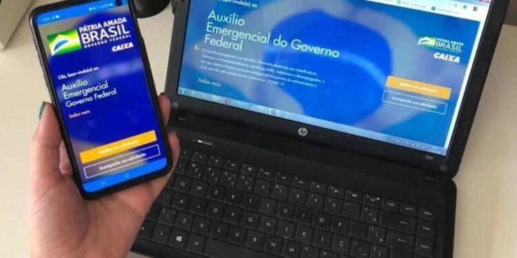 auxílio emergencial permanente: a imagem mostra mão segurando celular aberto no app do auxílio emergencial ao lado de computador aberto no site do auxílio emergencial