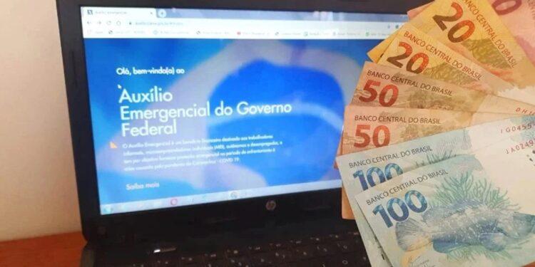 penhorar o auxílio emergencial: a imagem mostra leque de dinheiro à direita e computador aberto no site do auxílio emergencial ao fundo