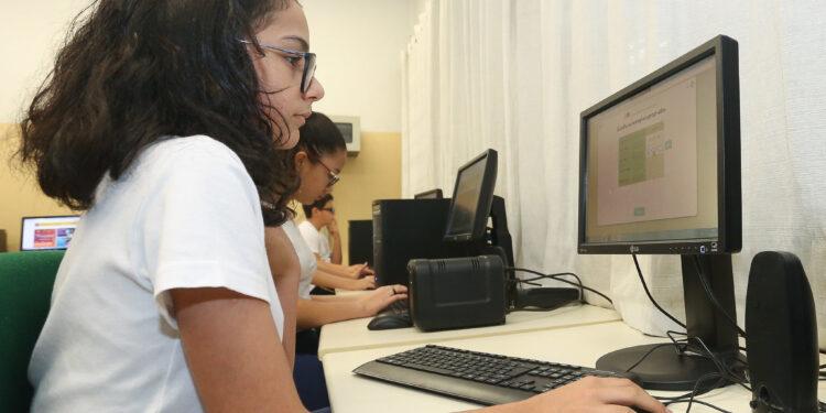 internet de qualidade nas escolas: a imagem mostra menina em primeiro plano mexendo no computador e ao fundo outras crianças fazendo o mesmo