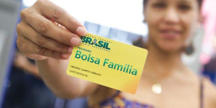 novo bolsa família: a imagem mostra mulher segurando o cartão do bolsa família