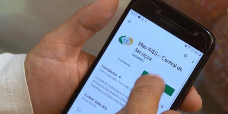 prova de vida: a imagem mostra mãos segurando celular baixando o app Meu INSS
